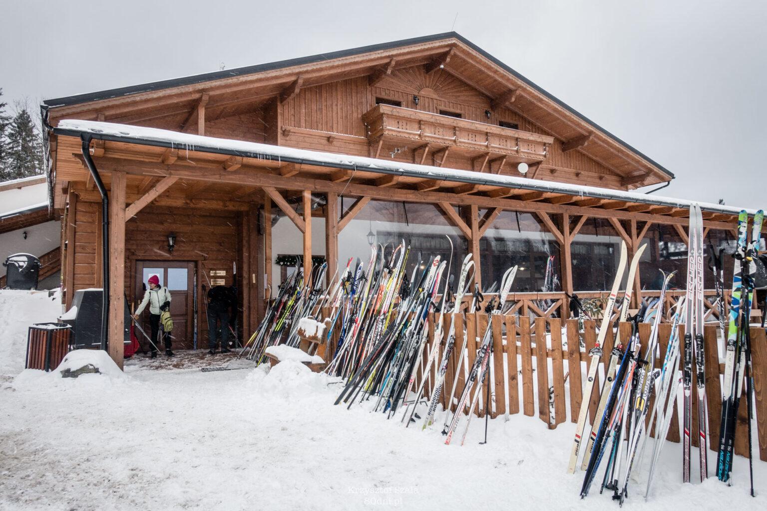 Hotel Martiňák z duża ilością nart biegowych przed wejściem.