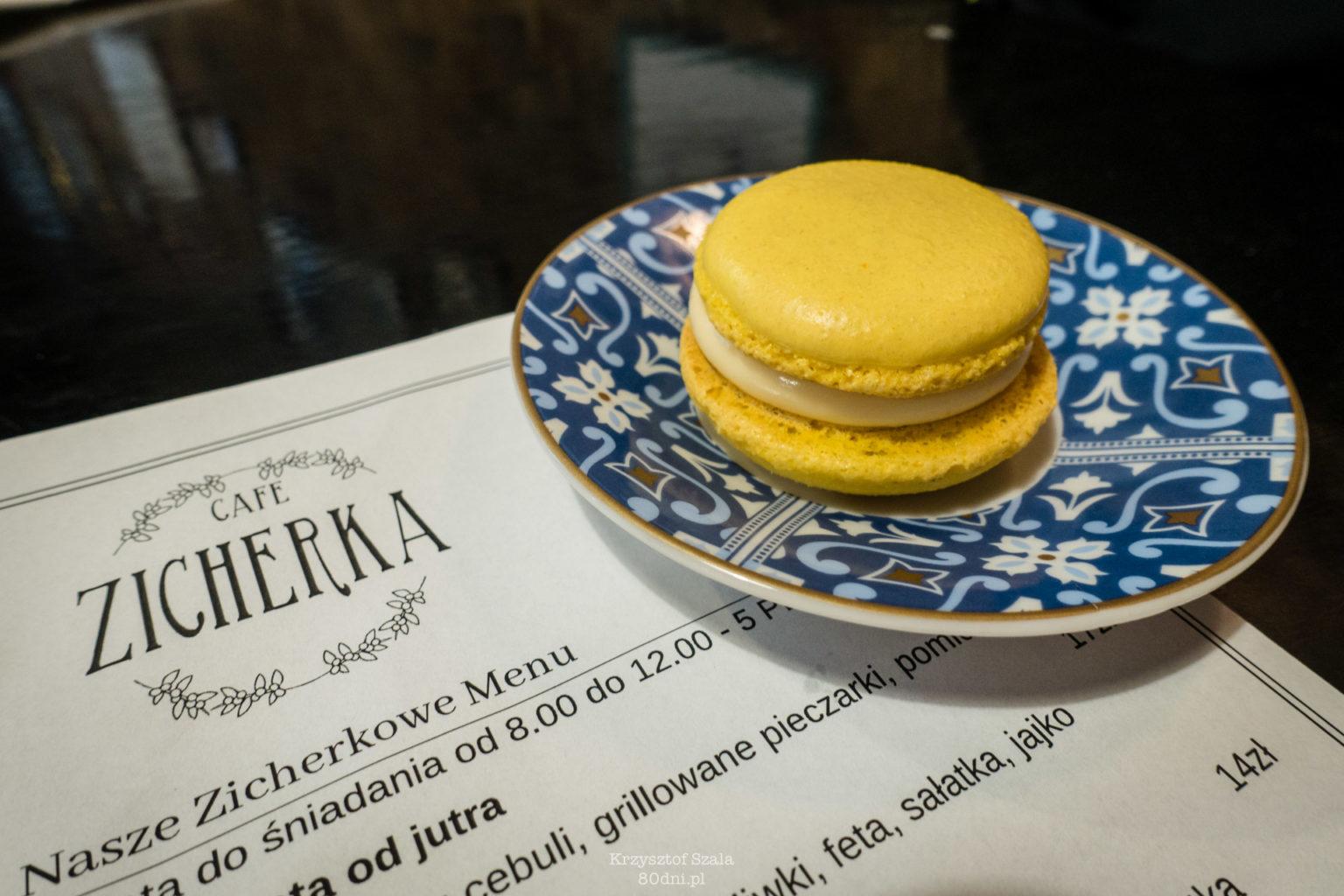 Zdjęcie makaronika cytrynowego na małym talerzyku oraz fragment menu.
